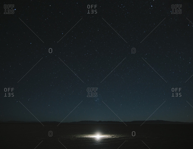 Glowing bright light on playa, night sky and Milky Way above, Black Rock Desert, Nevada