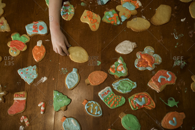 Child's hand reaching for Christmas cookie