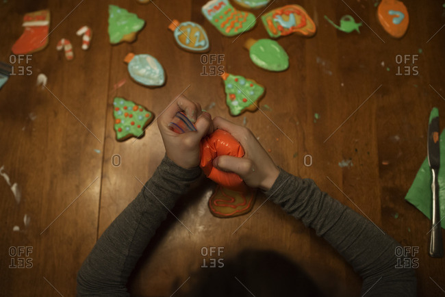 Overhead view of child decorating Christmas cookies