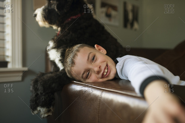 Young boy on sofa with pet dog