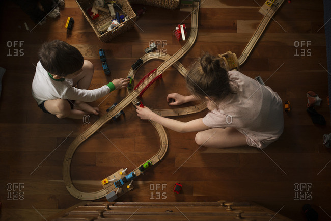 Overhead view of two young children playing with toy trains
