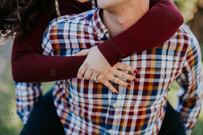 Woman with arms wrapped around her fiance