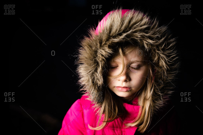 Girl in hooded coat with black background