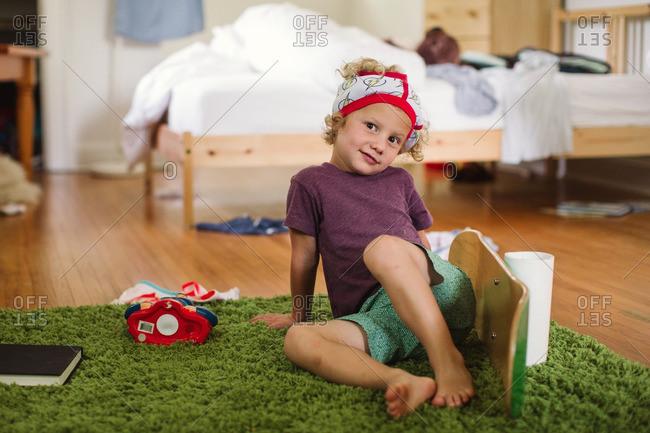 Boy sitting on green rug with underwear on head