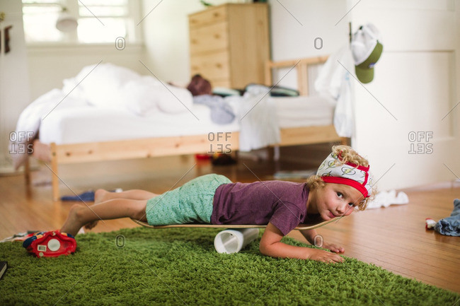 Boy lying on a skateboard with no wheels balanced on cylindrical tube