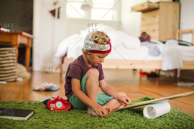 Boy with underwear on head sitting on rug and playing with toys