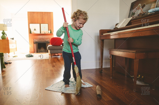 Boy holding broom standing on towel