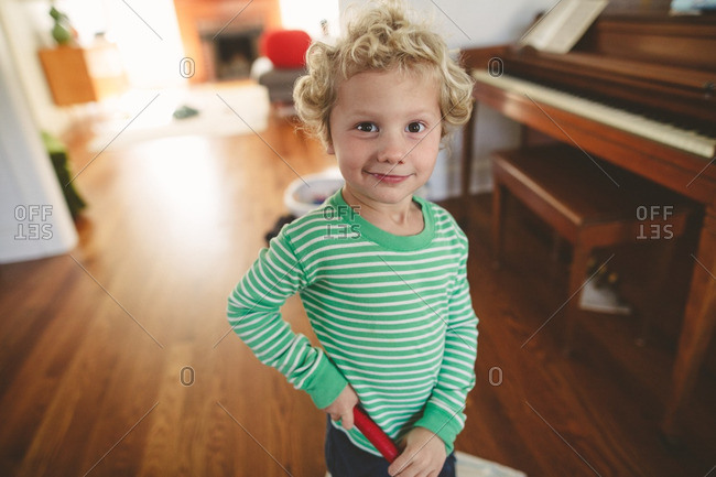 Portrait of a boy with curly blonde hair inside house