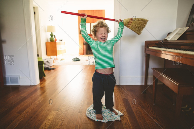 Little boy holding broom above head