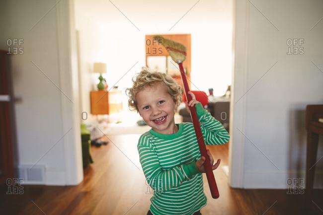 Smiling boy holding broom over shoulder