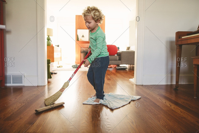 Boy holding broom standing on cleaning cloth