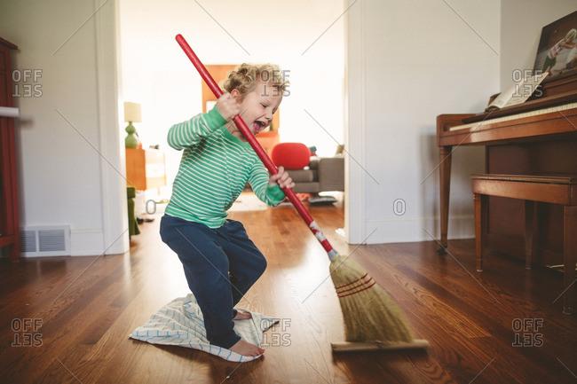 Boy playing with broom on hardwood floor