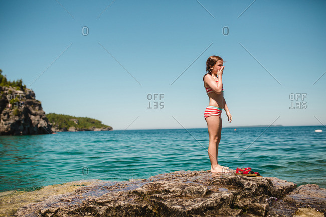 Girl with hand on face standing on rocky shore