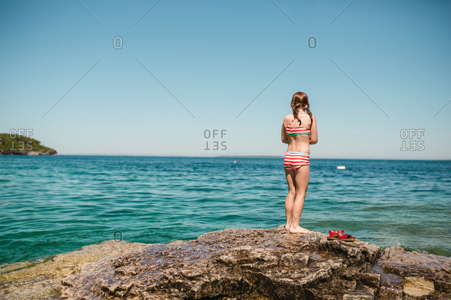 Girl in bathing suit standing on rocky shore looking out over ocean
