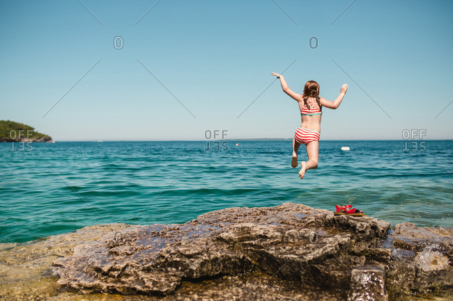 Girl jumping into the ocean from rocky shore