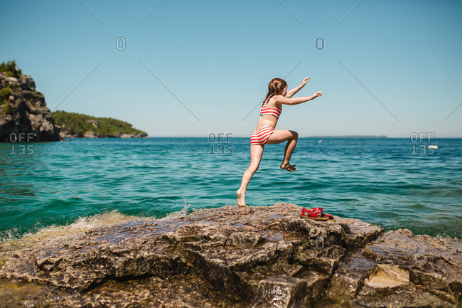 Girl about to jump into the ocean from rocky shore