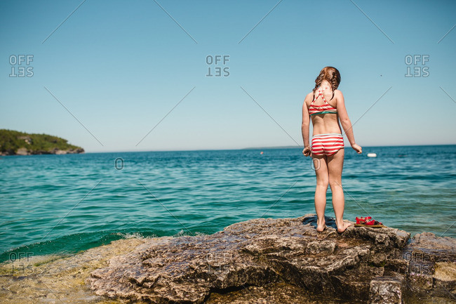 Girl standing on rocky shore looking down at water