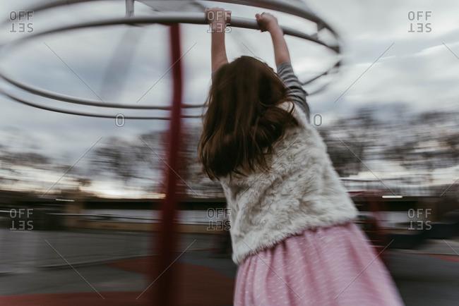 Girl spinning on playground equipment