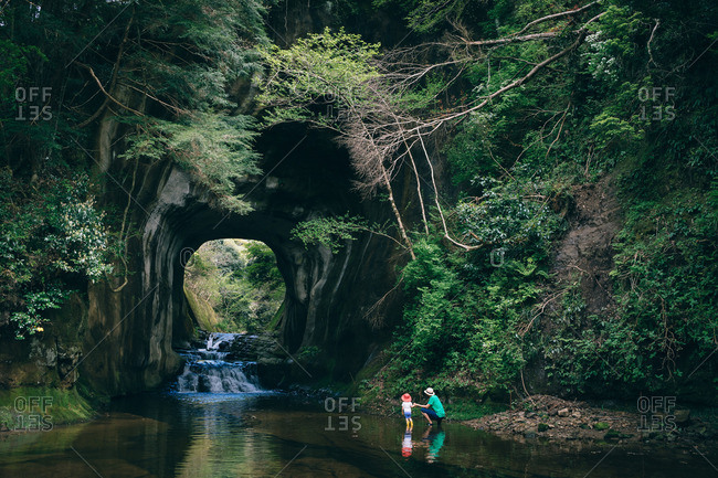 Woman holds child's hand as they gaze at waterfall through tunnel in river