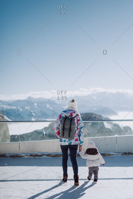 Woman and child overlooking snow covered mountain range