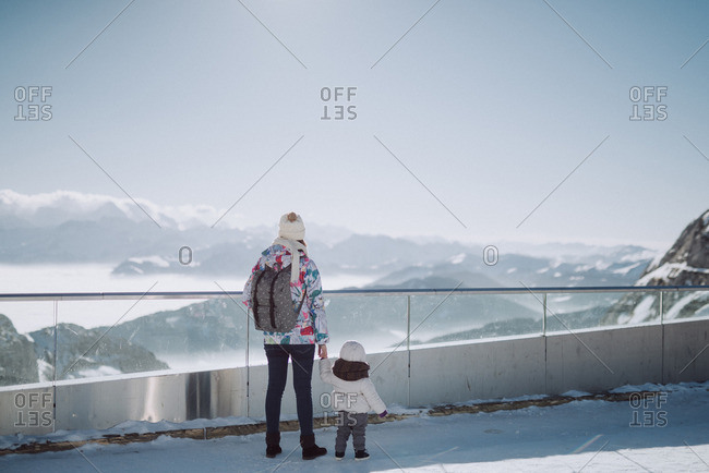 Woman and toddler overlooking snow covered mountain range