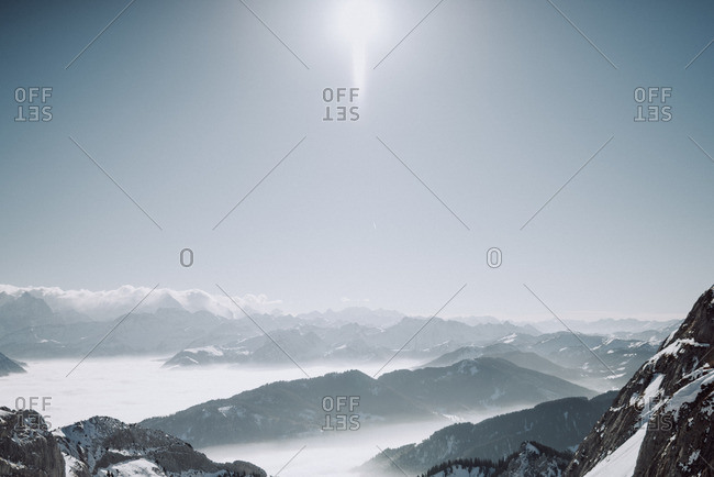 Sun shining over snowy mountain landscape