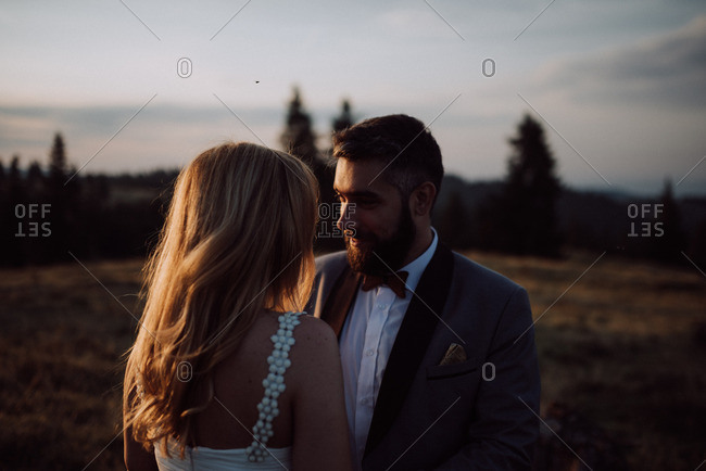 Groom wearing wooden bowtie and sunglasses smoking