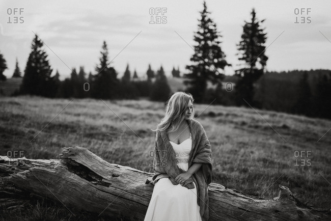 Bride sitting on a log wrapped in a blanket in black and white