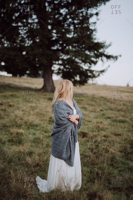 Bride standing in a field wrapped in a blanket
