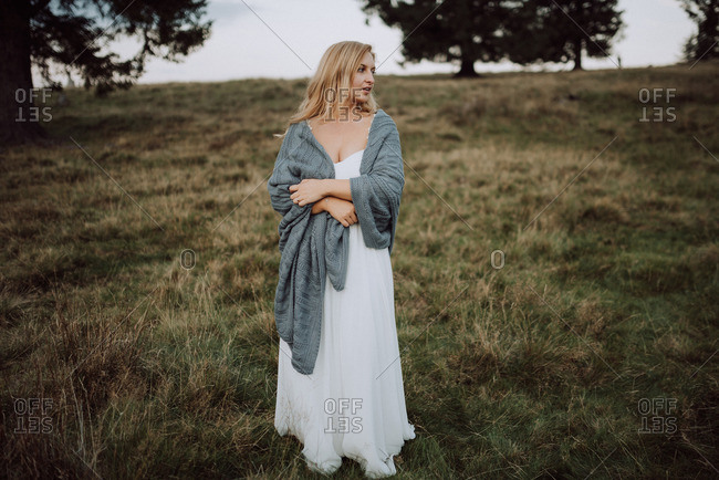 Blonde bride standing in a field wrapped in a blanket