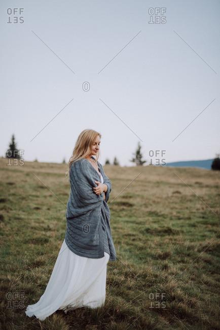 Bride walking in a field wrapped in a blanket