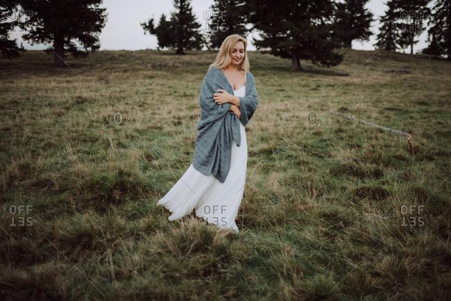 Bride walking alone in a field wrapped in a blanket