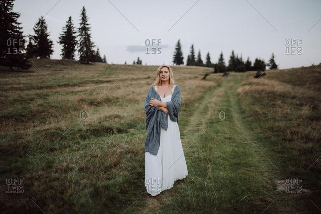 Blonde bride walking in a grassy field wrapped in a blanket