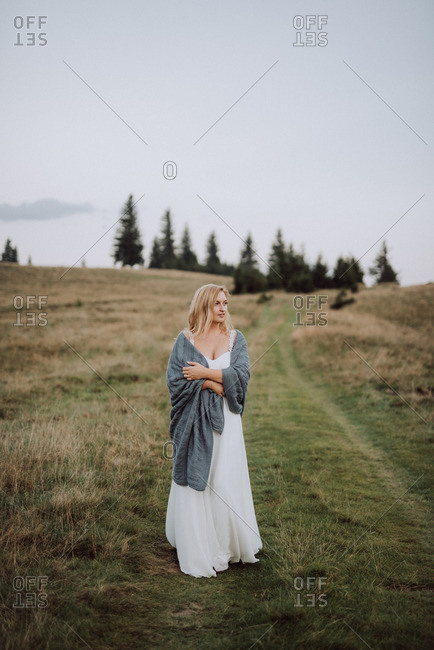 Blonde bride standing in a grassy field wrapped in a blanket