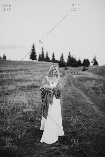 Blonde bride standing in a field wrapped in a blanket in black and white