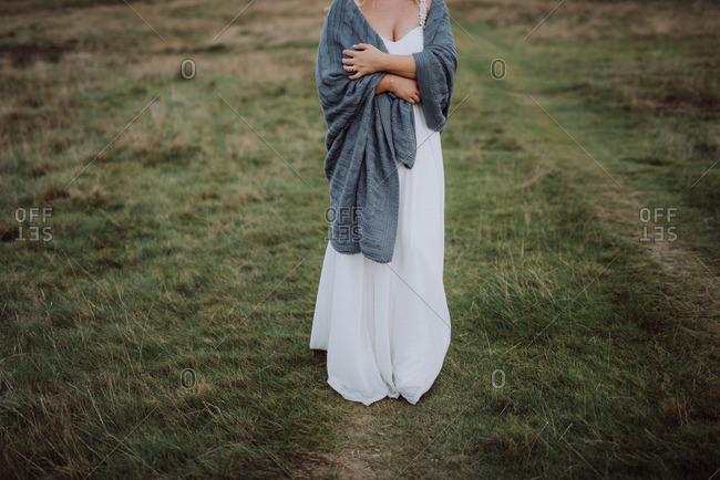 Bride wrapped in a blanket in the countryside