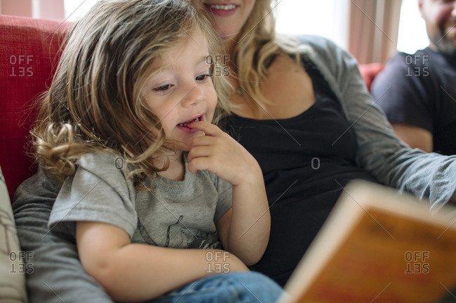 Parents reading with a girl