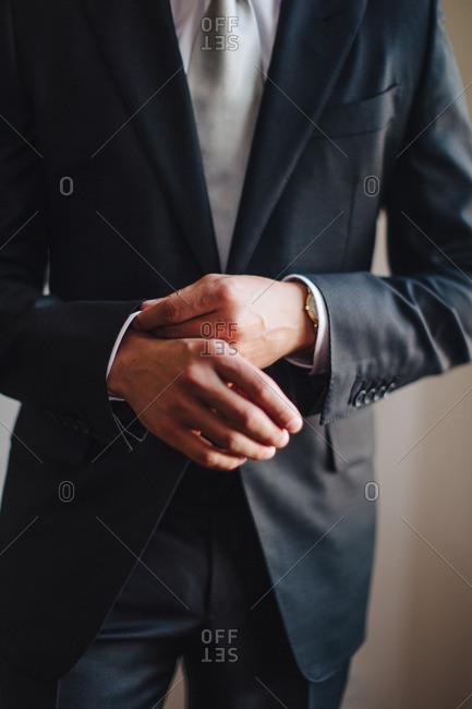 Man adjusting his suit sleeve