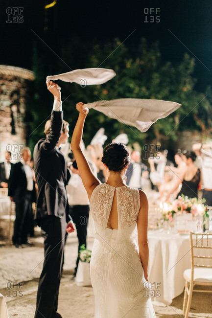 Bride and groom waving napkins