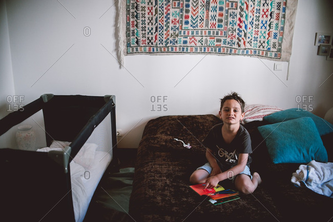 Boy reading books on futon at home