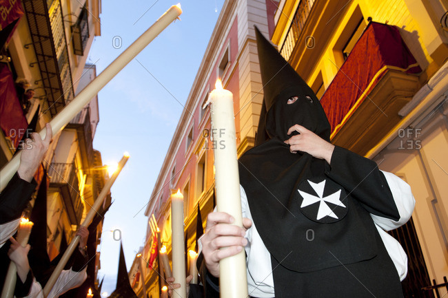 People dressed in hooded robes carrying tall candles at an Easter procession in Seville, Spain
