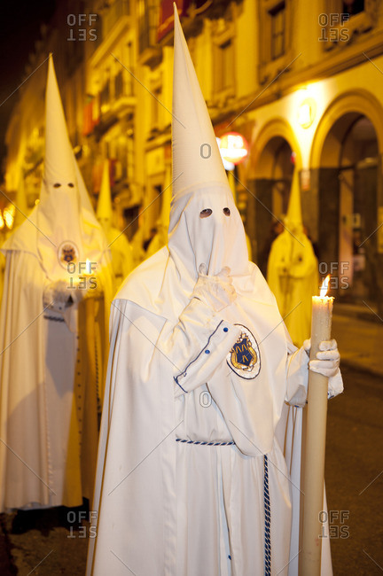 Priests in hooded white robes carrying tall candles at an Easter procession in Seville, Spain