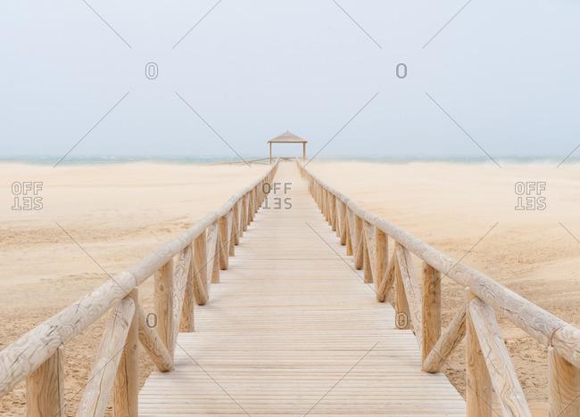 Boardwalk leading to a cabana on a beach