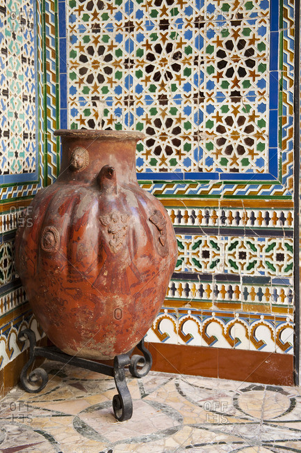 Clay urn in the corner of walls decorated with mosaic tiles