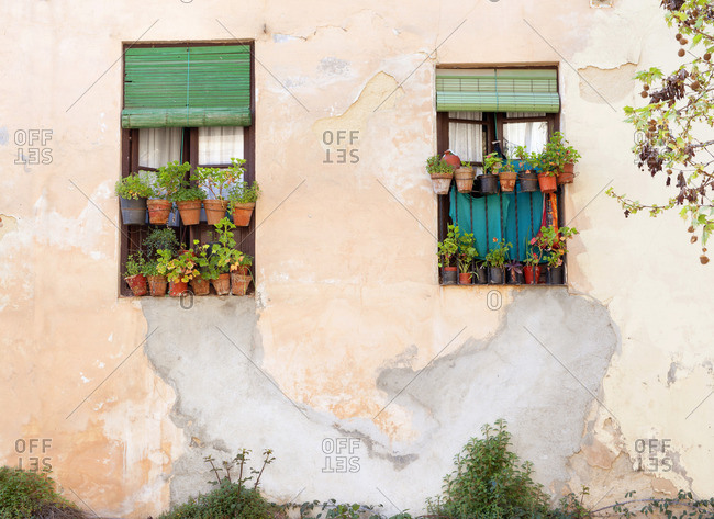 Terra cotta pots filled with plants in the windows of a home in Granada, Spain