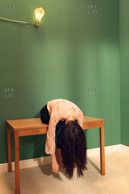 Fashionable young woman dangling from a table