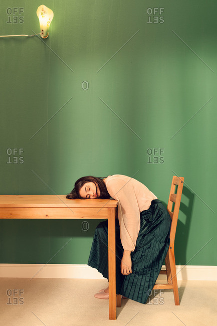 Woman sleeping on a table while sitting in a chair