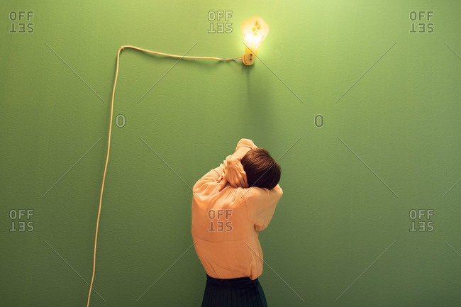 Woman standing under a sconce