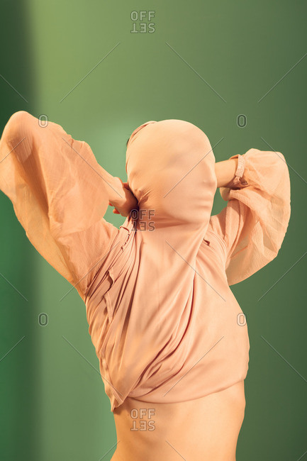 Woman covering her face with her blouse