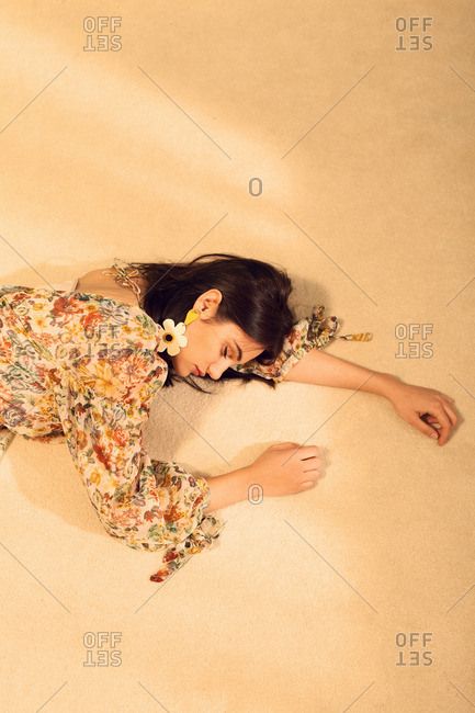 Brunette woman lying down on a carpet